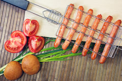 Grill-grate for sausages and tomato, bread, onions Stock Photos