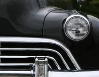 Grill and headlights. Photograph of an old classic car in mint condition, frontal shot with one headlight and grill, black and chrome finish Stock Photos