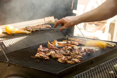 Grill. Man fries grilled meat, white sausages and corn in his hand tongs on iron gratings Stock Photos