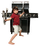 Grill Master. Adorable seven year old boy with grill utensils in front of large gas grill Royalty Free Stock Photos