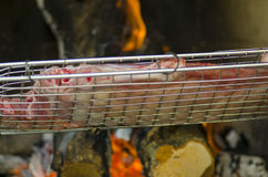 Grill with meat for barbecue fire in background. Grill with meat for barbecue and fire in background for dinner royalty free stock image