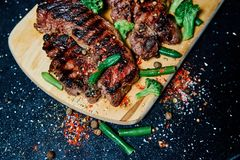 Grill meat steak pork with green beans on a wooden Board. Dark background. Photo for restaurant, cafe, bar menu. Top view stock image