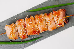 Grill meat on a wooden skewer with green onions on a white backg Stock Images