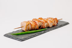 Grill meat on a wooden skewer with green onions on a white backg. Pieces of meat on a wooden skewer with green onions on a white background Royalty Free Stock Image