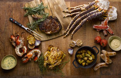 The grill mezza table meal with roasted chicken, beef, lobsters, sausages, king crab, potatoes, toamtoes, onion, garlic and chili royalty free stock image