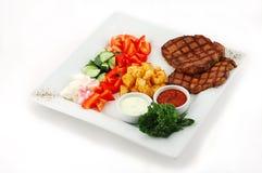 Grill mit Salat auf einer quadratischen Platte Stockfotografie