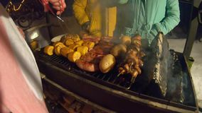 Grill na powietrzu Piec mięso, kiełbasy i warzywa na ogieniu, Gotować przy zima wieczór Ludzie stoi wokoło BBQ Dym od zbiory wideo