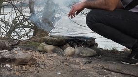 Grill outdoors near the river. Grill made with his own hands made of stone. A man with a cigarette on the riverside bonfire on a. Makeshift grill made of stone stock footage
