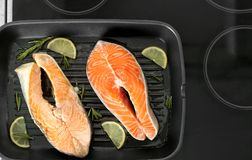 Grill pan with delicious salmon steaks on stove Stock Photos