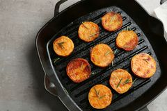 Grill pan with sweet potato fries on grey background. Top view royalty free stock photo