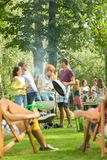 Grill party held in a park. By a large group of friends enjoying the warm weather and food Royalty Free Stock Photography