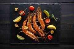 Grill piec na grillu krewetki z korzennymi składnikami czosnek i pomidor na ciemnym drewnianym stole zdjęcia royalty free