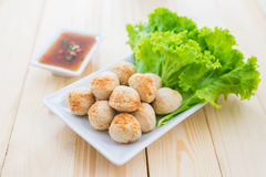 Grill pork balls with sweet spicy sauce on wooden table Royalty Free Stock Photos