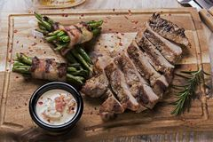 Grill pork steak with green beans with bacon on a board. A Royalty Free Stock Photos