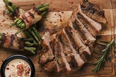 Grill pork steak with green beans with bacon on a board. A stock images