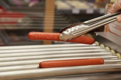 Grill sausage fast food. Grilled sausages hottest salesman took the tongs for the grill Royalty Free Stock Photo