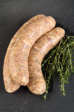 Grill sausage with herbs in natural casing. With thyme on a slate plate stock photography