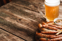 Grill sausages mix with beer, free space on wood. Mug of light beer and plate with various grilled sausages, close up view. German bar menu photo. Wooden Royalty Free Stock Photos