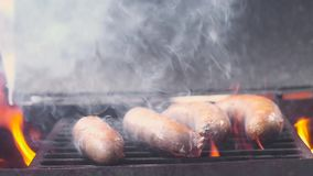Grill the sausages. Pork sausages on the hot grill on the barbecue.  Lots of smoke and fire. Close-up, slow motion.  stock video