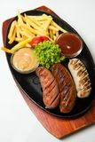Grill sausages on the wooden plate with french fries and sauces. White background. Stock Image