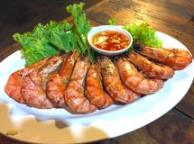 Grill shrimps with leaves of a green salad and garlick sauce on a plate.  Royalty Free Stock Image