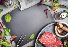 Grill steak ingredients around  blank chalkboard. Grill or BBQ steak marinating with Barbecue sauce. And basting brush on stone table background, top view Stock Images