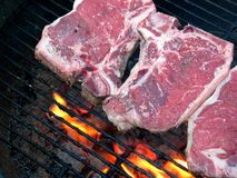 On the Grill T-Bone. Grilling the T-Bone Steak, with flame and charcoal, just placed, rare Royalty Free Stock Images