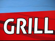 Grill writing at red table with blue background Royalty Free Stock Photo