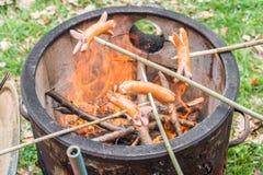 Grill z pożarniczym garnkiem i niektóre kiełbasami na kijach Obrazy Stock