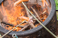 Grill z pożarniczym garnkiem i niektóre kiełbasami na kijach Fotografia Stock