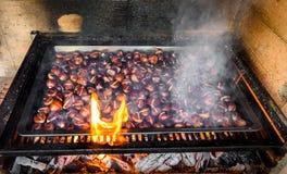 Grilla grillade kastanjer på grillfest med flammor, brand och cha Royaltyfri Fotografi