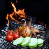Grilla hönsvaktlar och nya saftiga grönsaker i en restaurang Arkivfoton