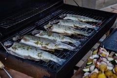 Grilla hela fiskar på spisgallret i trädgård Grilled marinerade nya foreller över kolen på grillfestgaller på sommartid Arkivfoton