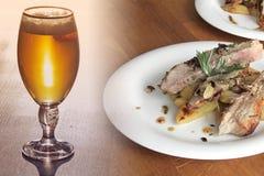Grilla kött med potatisar och ett exponeringsglas av öl arkivbilder