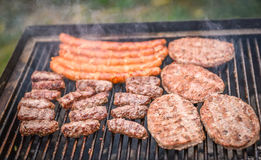 Grilla kött på grillfestgaller med kol arkivbild