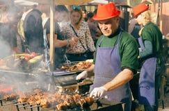 Grilla kocken som förbereder kött som är utomhus- under gatamatfestival Royaltyfri Bild