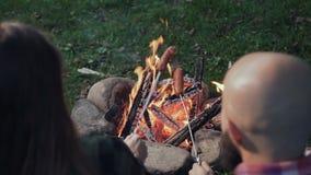 Grilla korvar över en lägereld, campare som grillar korvar Turister sitter nära flamman lager videofilmer
