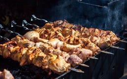 Grilla marinerad shashlik som förbereder sig på ett grillfestgaller över kol Shashlik är en form av kebaben Arkivbild