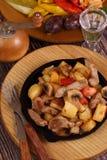 Grilla med en potatis, kött och champinjoner och ett vodkavin-exponeringsglas Royaltyfri Bild