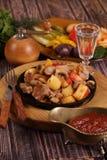 Grilla med en potatis, kött och champinjoner och ett vodkavin-exponeringsglas Royaltyfri Foto