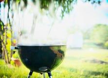 Grilla med rök över den utomhus- naturen för sommar i trädgård eller parkera, utomhus- arkivbilder