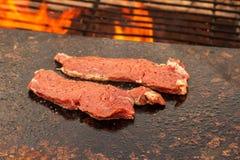 Grilla nötköttbiff på en granitplatta Förberedelse av kött på en utomhus- brand Sommargrillfest royaltyfri foto