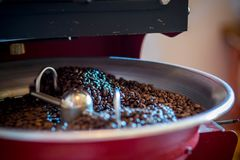 Grilla och blandande grillat kaffe i en kaffebrännare royaltyfri bild