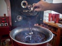 Grilla och blandande grillat kaffe i en kaffebrännare arkivfoton