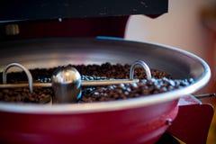 Grilla och blandande grillat kaffe i en kaffebrännare arkivbilder