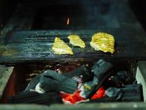 Grilla process Glödande vedträ bredvid tre saftiga stycken av grillad höna Den svarta bränningen loggar in ett suddigt fotografering för bildbyråer