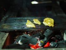 Grilla process Glödande vedträ bredvid tre saftiga stycken av grillad höna Den svarta bränningen loggar in ett suddigt royaltyfri fotografi