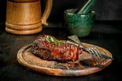Grilla saftig nötköttT-benet biff med salt peppar och rosmarin Royaltyfri Bild