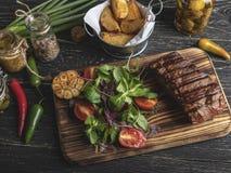 Grillad biff på brädet som tjänas som med örter, stekte potatisar, kryddor på en svart yttersida arkivbild