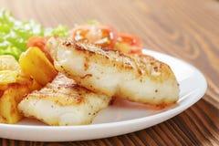 Grillad codfishfilé med grönsaker Fotografering för Bildbyråer